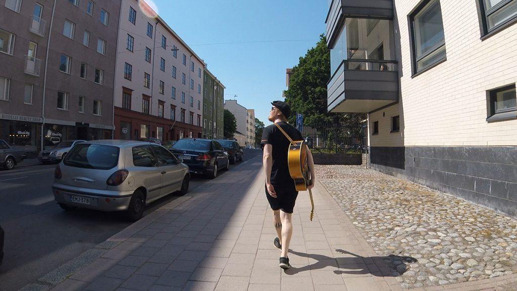 Nuori mies ja kitara hakevat innoitusta kaupunkimiljööstä.