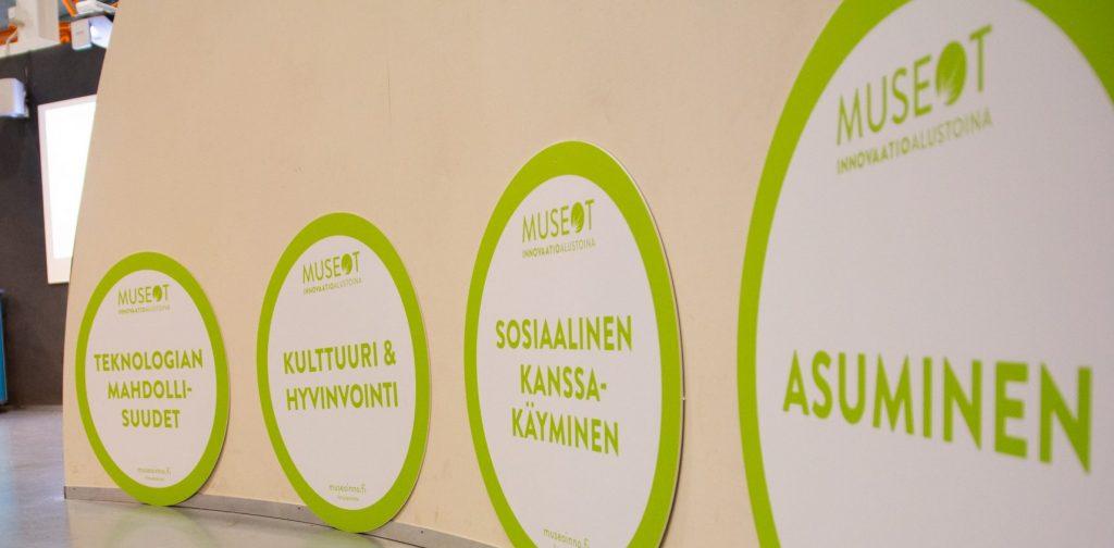 Seinä käytävällä, johon on kiinnitetty pyöreitä julisteita, joissa lukee