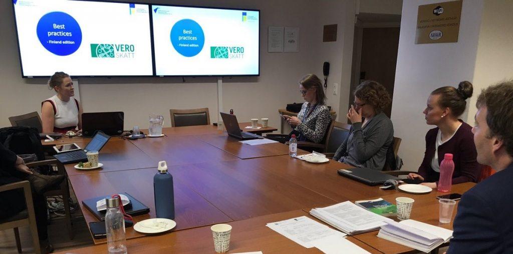 Henkilöt ovat kerääntyneetn pöydän äärelle keskustelemaan. Taustalla Verohallinnon logo.