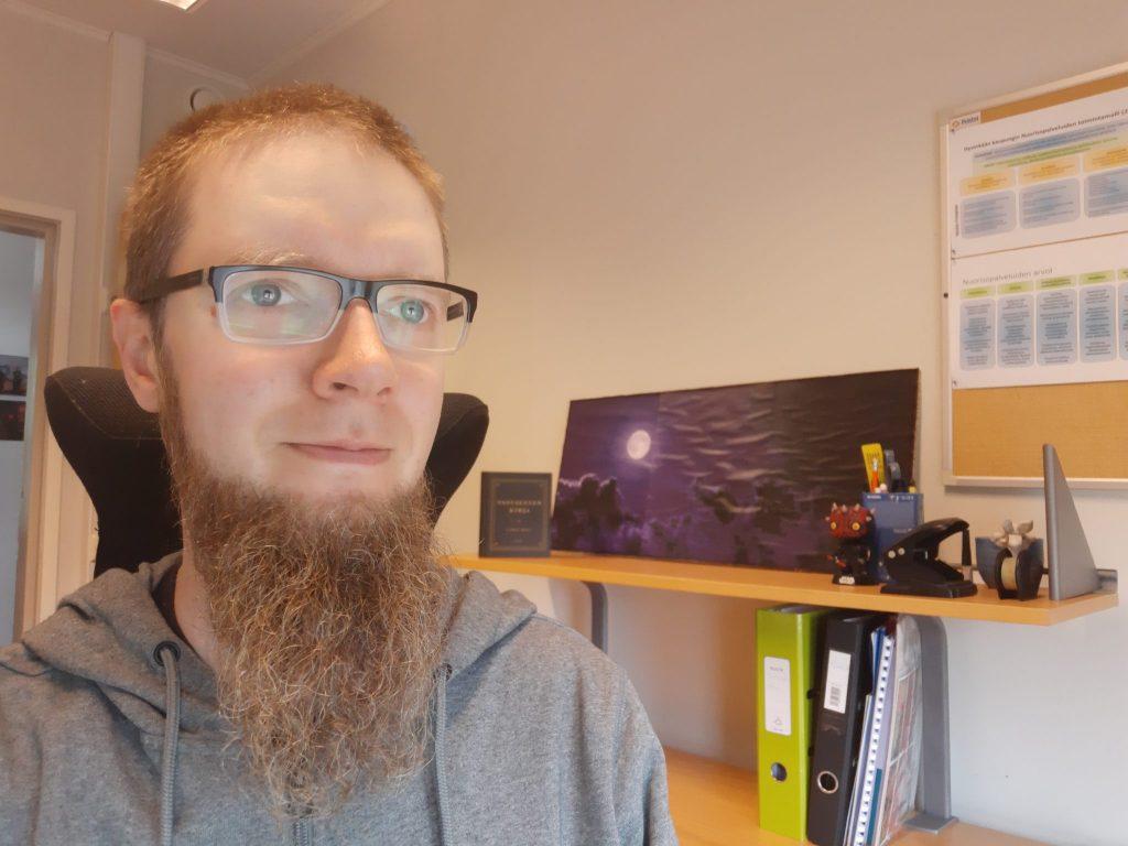 Parrakas mies silmälaseissa poseeraa työpöydän äärellä, selfie.