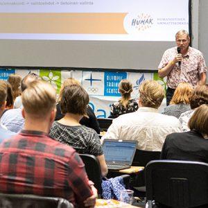 Mies seisoo mikrofoni kädessään luokan edessä ihmisten kuunnellessa tarkkaavaisina. Taustalla powerpoint, jossa näkyy Humanistinen amk:n logo.