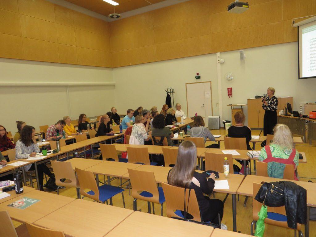 Luokkahuoneessa ihmisiä istuu pöytien äärellä ja kuuntelevat etualalla puhujaa.