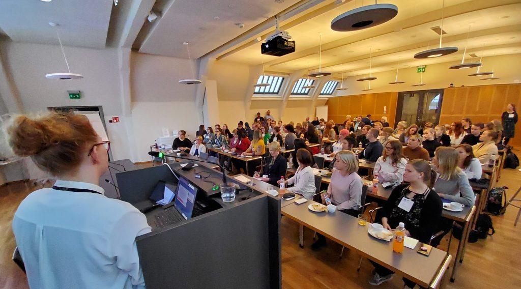 Paljon henkilöitä istumassa luokkahuoneessa, kuvan etualalla henkilö puhujapöntön takana.