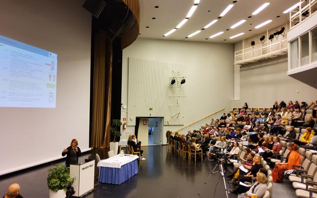 Luentosali, joka on täynnä ihmisiä ja nainen puhuu mikrofoniin etualalla.