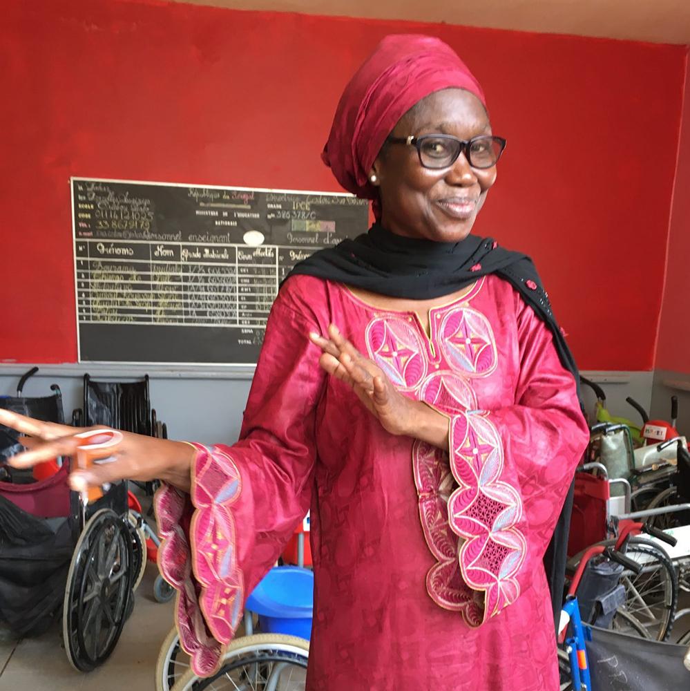 Värikkääseen afrikkalaiseen kaapuun pukeutunut nainen esittelee nuorten käyttämiä tavaroita varastossa.