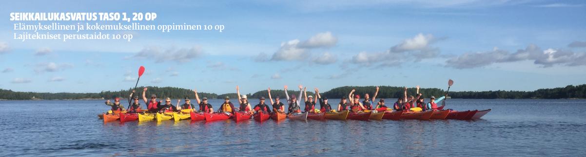 Kesäinen vesimaisema, jossa monta ihmistä rivissä eri värisillä kanooteilla.
