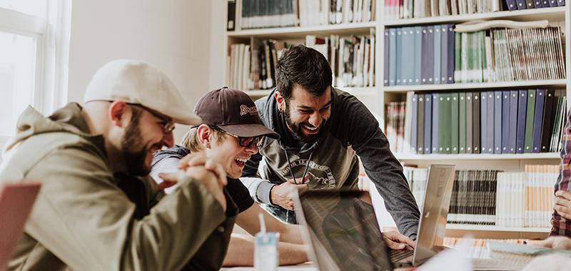 Kolme miestä seisovat kirjastossa tietokoneiden äärellä ja nauravat.