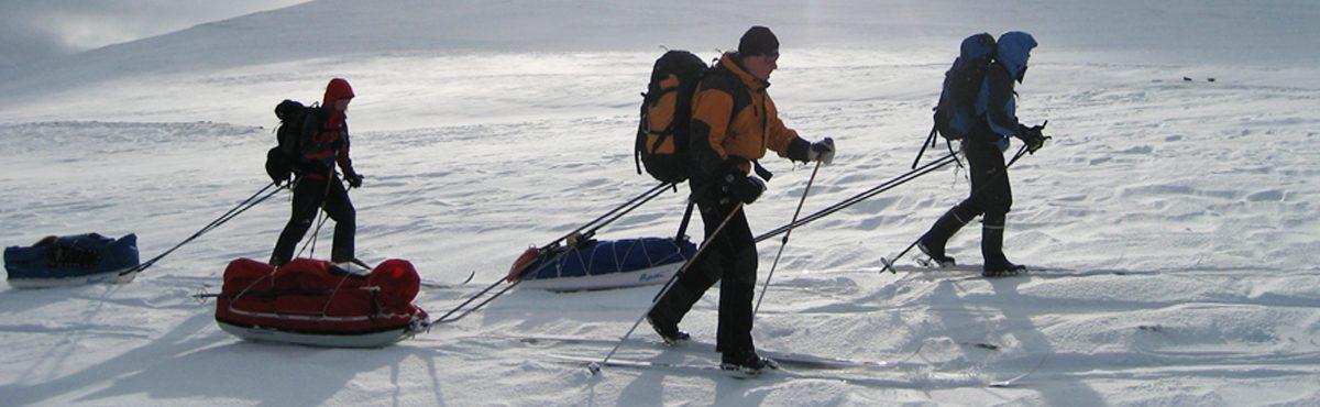 Kolme henkilöä talvivarustuksessa hiihtää.