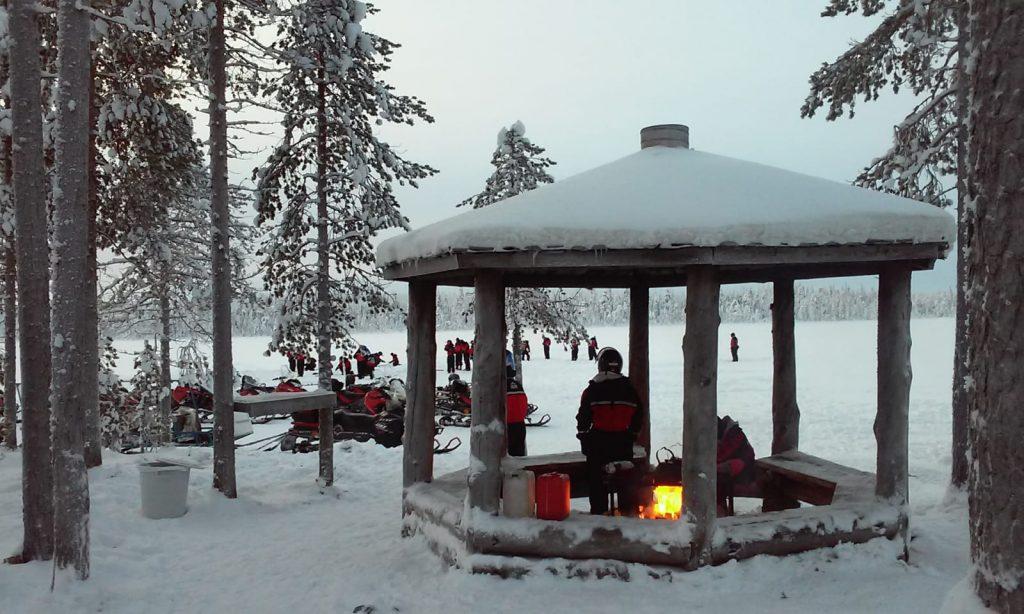 Luminen maisema, etualalla kuvassa katos, jonka sisällä on nuotio. Taustalla näkyy jäätynyt järvi sekä mooottorikelkkoja.