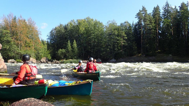 Henkilöt istuvat kanooteissaan ja vesi tyrskyää.