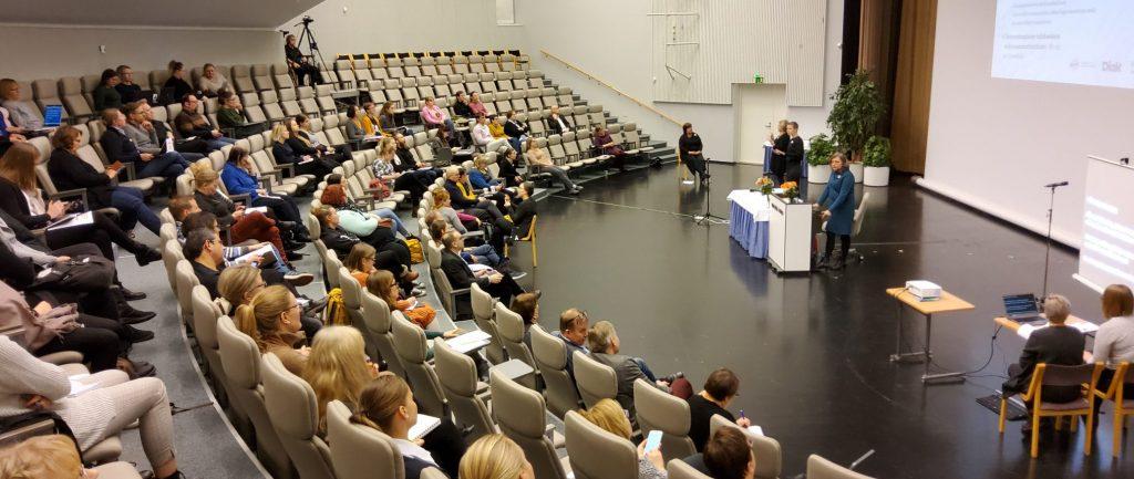 Seminaarisali, jossa kävijät istuvat tuoleilla ja kuuntelevat keskellä olevaa puhujaa.
