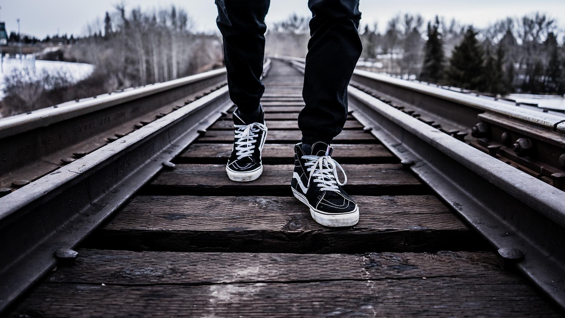 Kuvassa mies kävelemässä junarataa pitkin. Kuvituskuva.