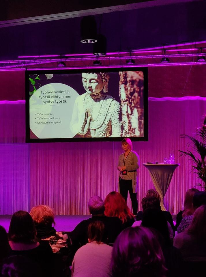 Työhyvinvoinnin seminaarissa otettu kuva, jossa puhumassa vaaleahiuksinen nainen.