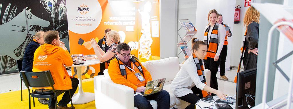 Kuva Nuori2020-päiviltä Tampere-talosta. Kuvassa Humakin messupiste, jossa ihmisiä pöydän ympärillä puhumassa.