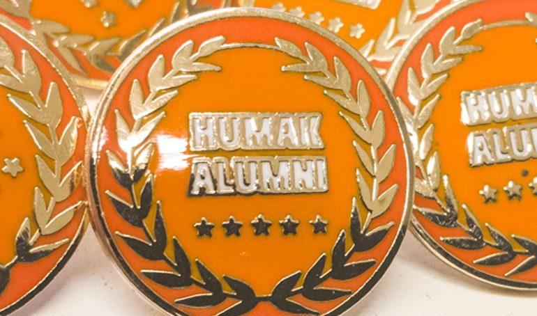 """Lähikuva Humakin alumnipinssistä. Pinssi on oranssi, jossa on kultaiset reunat, kultainen seppele ja teksti """"Humak alumni"""" ja viisi tähteä."""