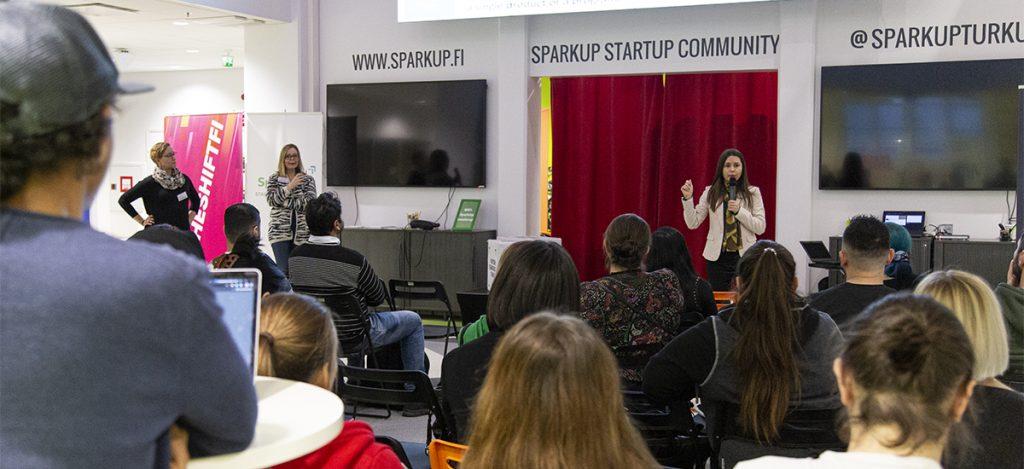 Tummahiuksinen nainen (Armela) puhuu mikrofoniin ihmisten keskellä.