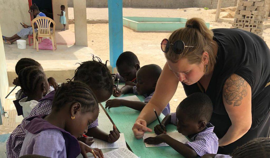 Anniina Ahlholm opettaa gambialaislapsille kirjoittamista.
