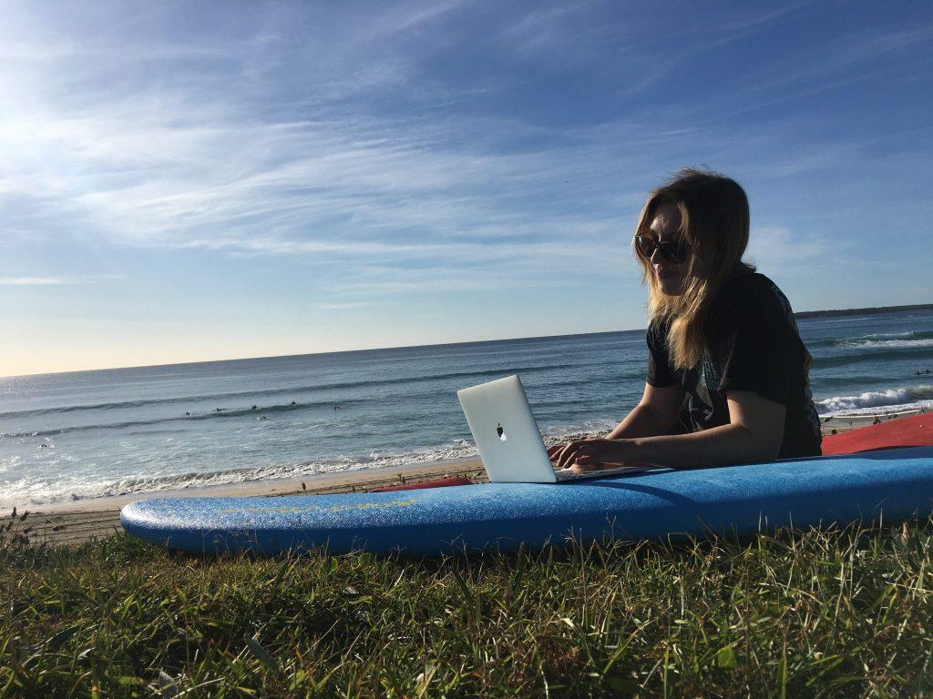 Henkilö istuu meren rannalla surffilaudan päällä ja kirjoittaa tietokoneella.
