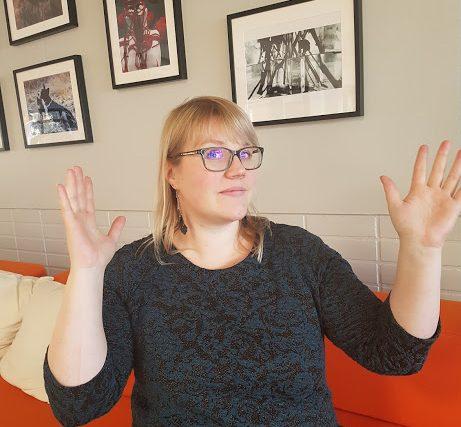 Vaaleahiuksinen nainen (Laura Pesonen) istuu sohvalla ja viittoo käsillään.