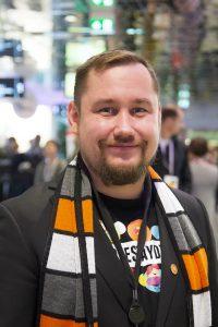 Kuvassa lyhyt hiuksinen mies (Ossi Ollikainen), jolla on partaa ja hymyilee. Taustalla on ihmisiä.