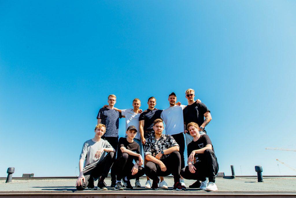 Yhdeksän miestä poseeraavat kahdessa rivissä rakennuksen katolla.