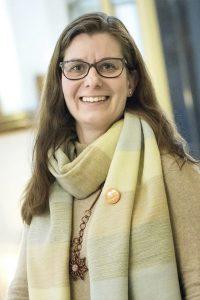 Kuvassa ruskeahiuksinen nainen (Työyhteisön kehittäjä koulutuksen lehtori Anu Järvensivu), jolla on silmälasit ja hymyilee.