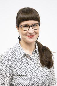 Kuvassa ruskeahiuksinen nainen (Työyhteisön kehittäjä koulutuksen lehtori Heli Heikkilä), jolla on silmälasit ja hymyilee.