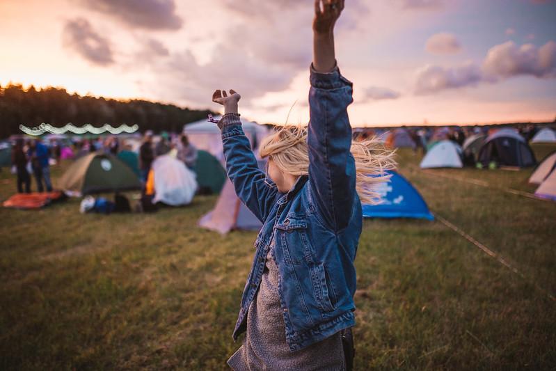 Tyttö juhlii festareiden leirintäalueella.