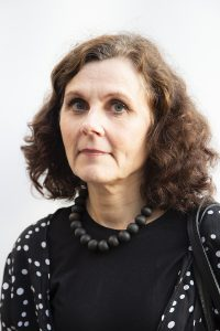 Kuvassa ruskeahiuksinen nainen (Työyhteisön kehittäjä koulutuksen lehtori Nina Simola-Alha), jolla on tummat vaatteet ja puuhelmet kaulassa.