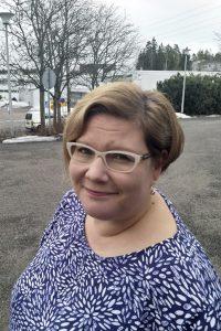 Kuvassa vaaleahiuksinen nainen (Työyhteisön kehittäjä koulutuksen lehtori Pauliina Parhiala), jolla on silmälasit ja hymyilee vienosti.