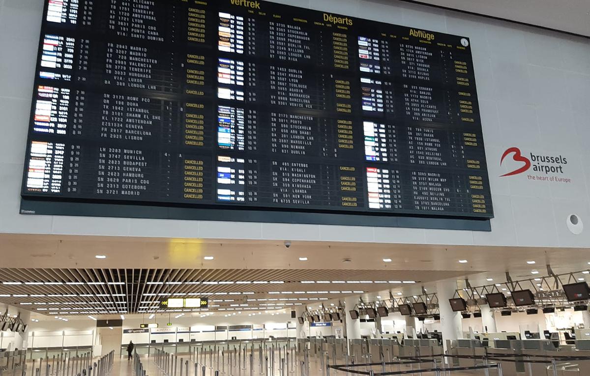 Kuvassa tyhjä Brysselin lentokenttä, jossa näkyy lentokentän aulaa sekä saapuvat/lähtevät lennot-ilmoitustaulu.