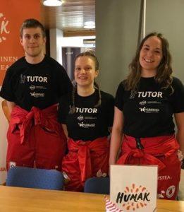 """Kolme tutoria (mies ja kaksi naista) seisovat pöydän äärellä ja hymyilevät kameralle. Kaikilla on päällä punaiset opiskelijahaalarit sekä musta paita, jossa lukee """"tutor""""."""
