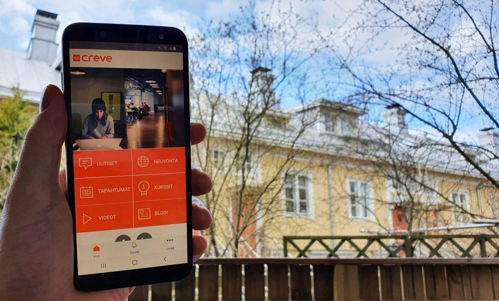 Henkilön kädessä on puhelin, jossa näkyy Creve-appin aloitusnäkymä.