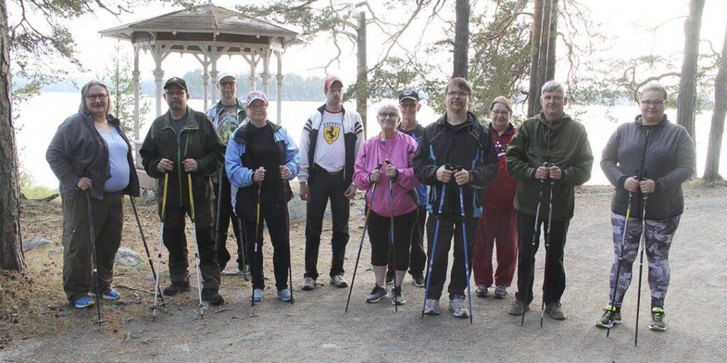 Ryhmäkuva, jossa 11 ihmistä poseeraa veden äärellä kävelysauvat kädessä.