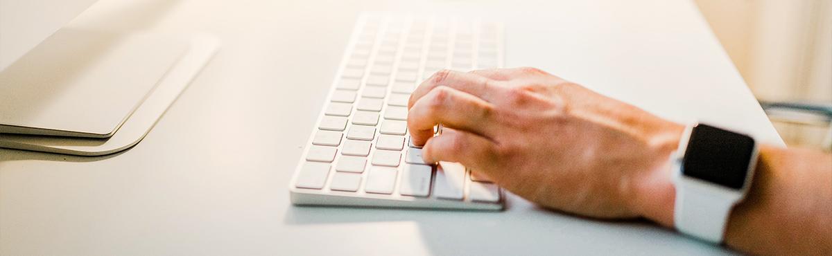 Valkoinen pöytä, jonka oikeassa reunassa tietokoneen näppämistö sekä käsi, joka kirjoittaa.