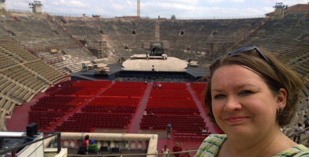 Kuvan oikeassa reunassa tummahiuksinen henkilö (Marika Stam) ja taustalla vanha stadion.