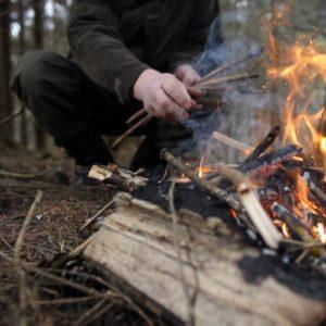 Henkilö on kumartunut nuotion vierelle laittaakseen sinne lisää puita.