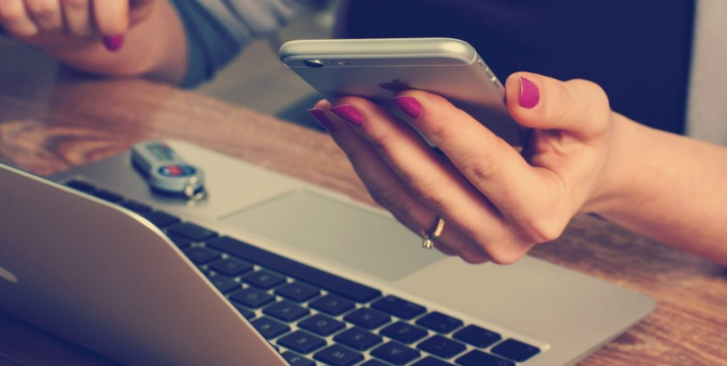 Nainen istuu pöydän ääressä, jossa on tietokone ja pitää puhelinta kädessään.
