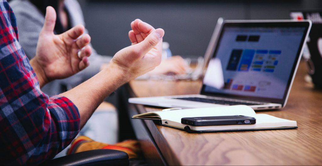 Nainen istuu pöydän äärellä jossa on avoin tietokone, puhelin ja lehtiö. Nainen tulkkaa käsillään.
