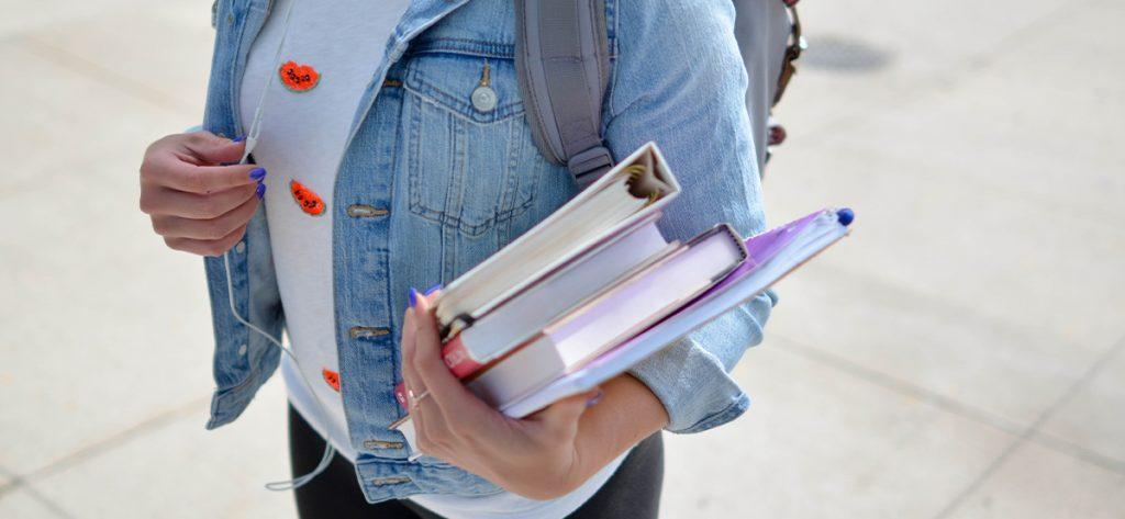 Kuvassa nainen farkkutakissa pitelemässä koulukirjoja.