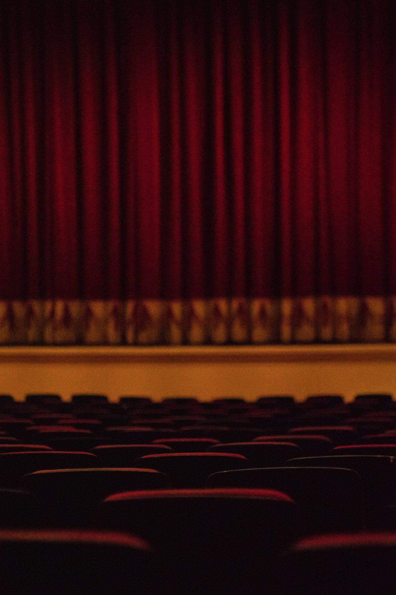 Kuvassa tyhjä teatterisali, jossa näkyy tyhjiä tuoleja sekä teatterin esirippu.