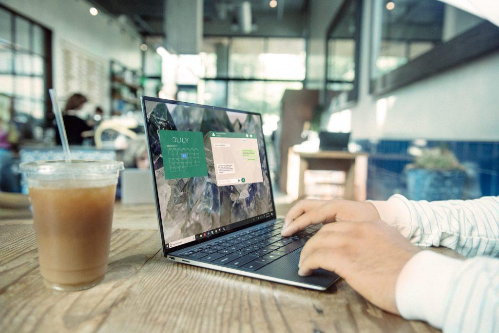 Tietokone, miehen kädet ja tietokone pöydällä avoimessa tilassa.