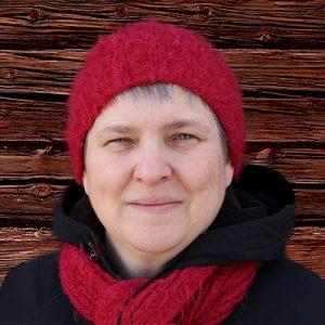 Nainen seisoo punaisen puuseinän edessä, päällään musta paita, punainen huivi ja punainen pipo.