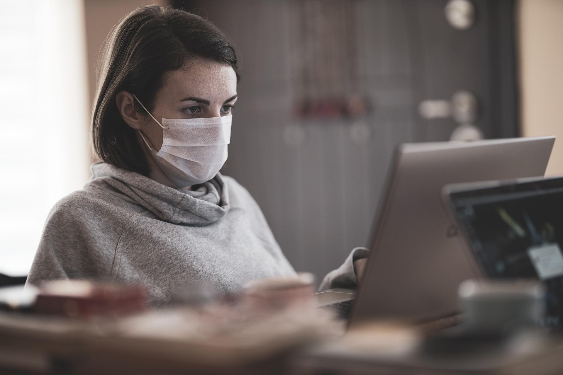 Tummahiuksinen nainen istuu tietokoneen äärellä, päässään kasvomaski.
