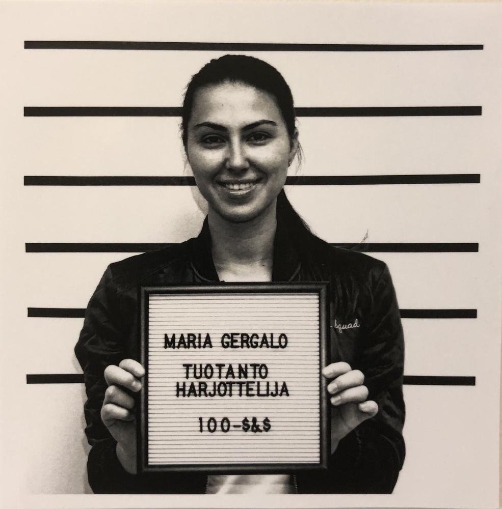 Nuori nainen hymyilee ja pitää kädessään kylttiä, jossa lukee Maria Gergalo, Tuotantoharjoittelija.