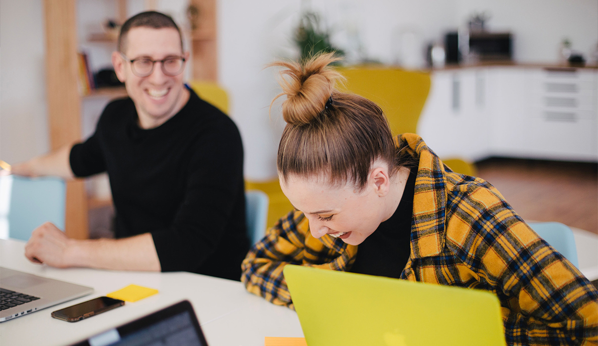 Nainen ja mies istuu työpöydän äärellä, jossa on tietokoneita ja muistiinpanovälineitä. Nainen nauraa.