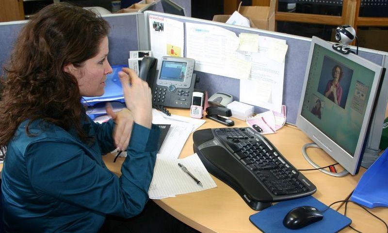 Etätulkkausta viittomakielellä. Nainen istuu sermin takana työpöytänsä ääressä. Hän viittoo tietokoneen näytön päälle kiinnitettyyn pieneen kameraan päin. Tietokoneen näytöllä näkyy kaksi viittovaa henkilöä omissa ruuduissaan, toinen heistä on viittova nainen. Naisen työpöydällä on muistiinpanopaperia ja kynä sen päällä; näppäimistö, hiiri, lankapuhelin ja kännykkä sekä toimistovälineitä.
