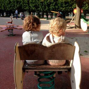 Kaksi-lasta-leikkipuistossa-selkakuva