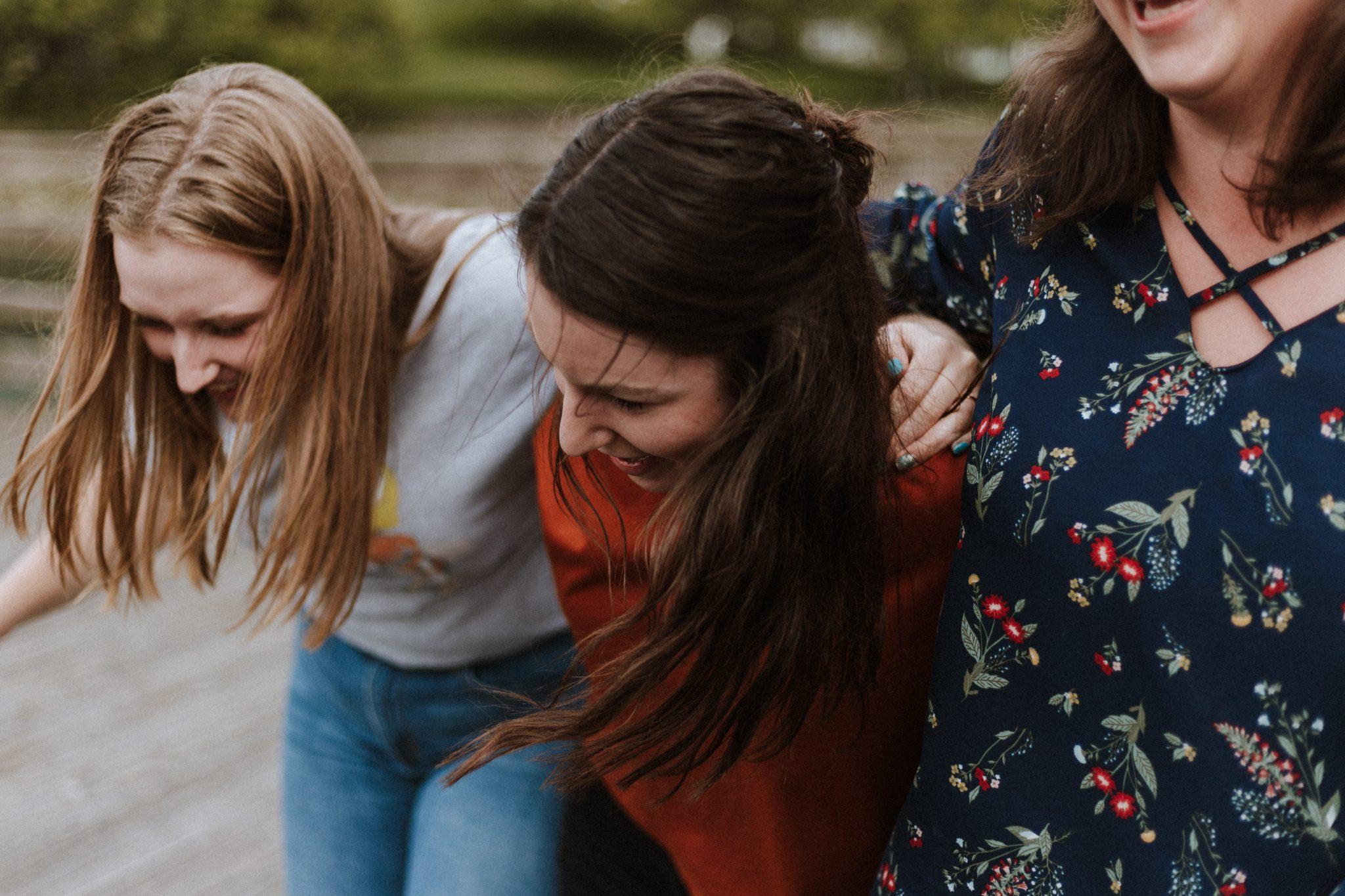 Kolme nauravaa tyttöä kulkevat käsi kädessä.