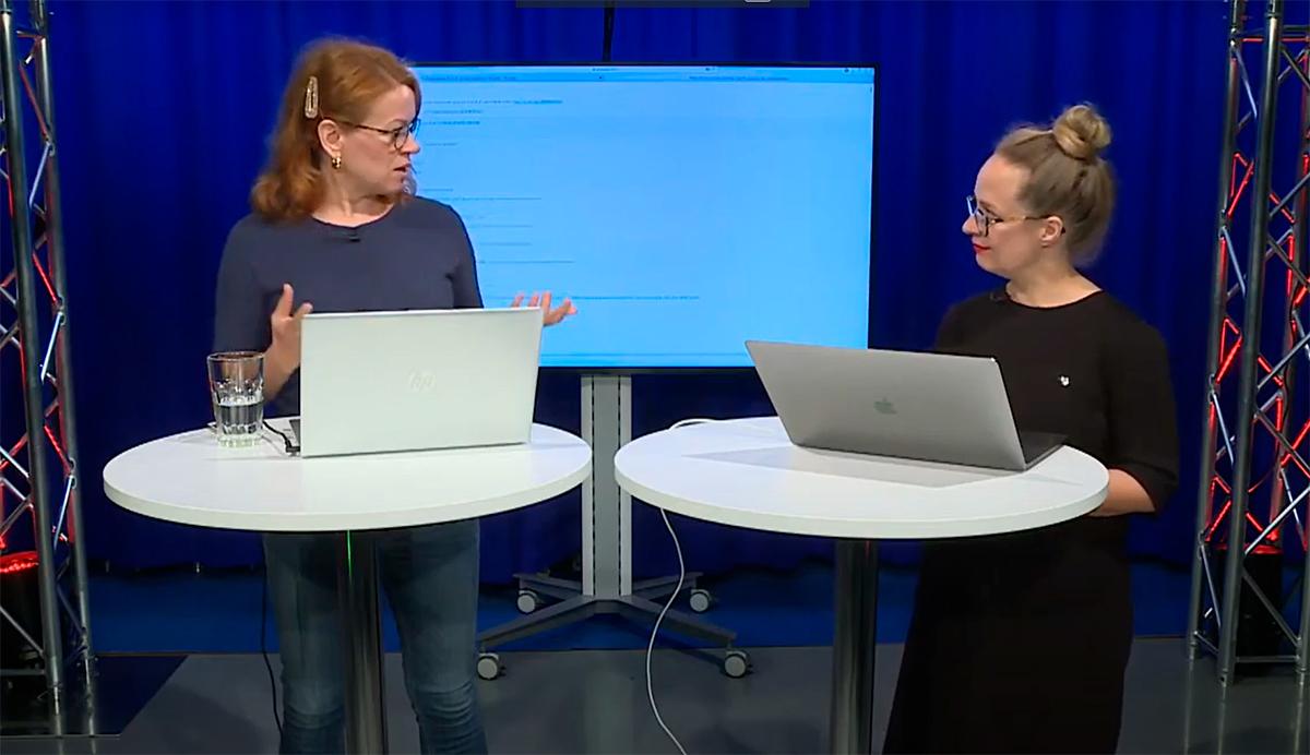 """ALT: YLE:n asiantuntijat Tiina Klemettilä ja Marja Ollikainen seisovat pöydän ääressä ja keskustelevat vuorovaikutuksen mahdollisuuksista verkkotapahtumissa. Blogi teksti """"Yleisön kohtaaminen""""."""